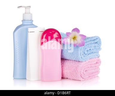 Shampoo and gel bottles with towels and flower. Isolated on white background - Stock Photo