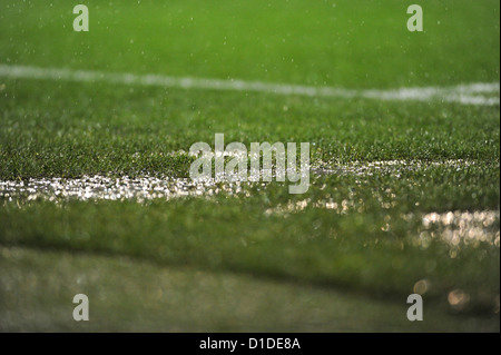 Heavy rain falling on waterlogged turf football pitch with standing water - Stock Photo