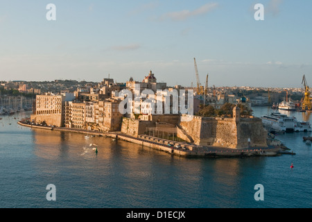 Early morning sunshine warms Fort St Michael and the fortified city of Senglea on the eastern shore of Grand Harbour, - Stock Photo
