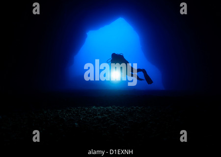 Diver in the entry of a cave, Mediterranean Sea near Gozo, Malta, underwater shot - Stock Photo