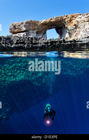 Split shot half and half with diver and rock arch Azure window in the Mediterranean Sea near Gozo, Malta - Stock Photo