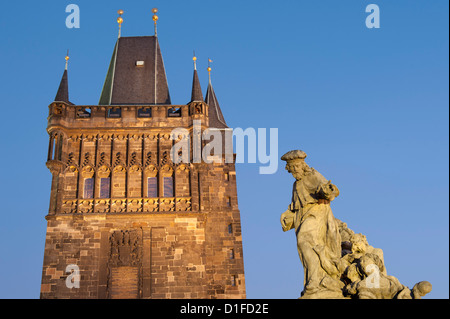 Town Bridge Tower and statue of St. Ivo (Bishop of Chartres) at twilight, Charles Bridge, Old Town, Prague, Czech - Stock Photo