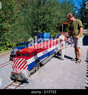 Father and Son admire Miniature Train Locomotive Engine at West Coast Railway Heritage Park, Squamish, British Columbia, - Stock Photo