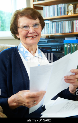 Senior woman at home with utility bills looking at camera and smiling - Stock Photo