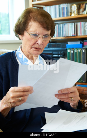 Senior woman at home reading utility bills looking worried and concerned - Stock Photo
