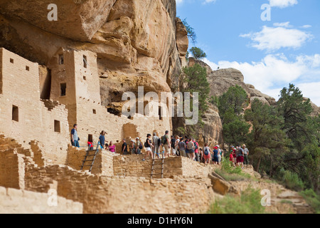 Tourists visit Cliff Palace cliff dwellings in Mesa Verde National Park, Colorado - Stock Photo