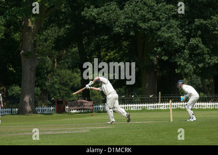 Game of cricket on a summers afternoon in an English village. - Stock Photo
