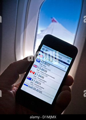iPhone 4s smartphone app displaying currency exchange rate in-flight, with business class cabin window wing and - Stock Photo