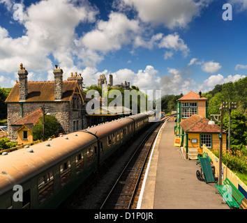 A steam train pulls in to the station at Corfe Castle in Dorset - Stock Photo