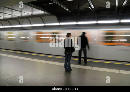 Passengers waiting for a fast moving U-Bahn train on a platform in Vienna, Austria. - Stock Photo