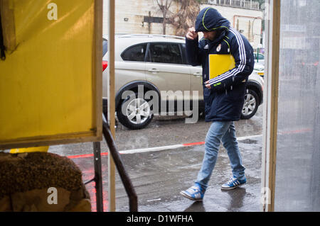 A man walks in the rain wrapped in a raincoat. Jerusalem, Israel. 7-Jan-2012.  An extreme winter storm raging nationwide - Stock Photo