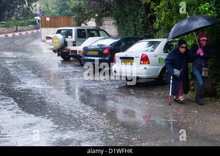 An elderly woman with a walking stick and her escort share an umbrella as they bypass a large puddle in the road. - Stock Photo
