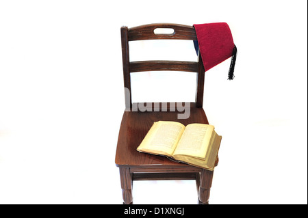 An old open book left open on an old chair. A middle eastern historic head cover (tarboosh) is hanging on the chair - Stock Photo