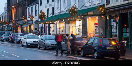Moffat town centre Christmas lights decorations along the shops and in the trees on High Street at dusk - Stock Photo