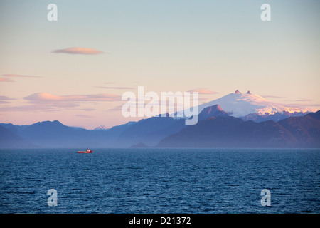 Fishing boat and snow-covered volcanic peak at sunset, Chilean fjords, Magallanes y de la Antartica Chilena, Patagonia, - Stock Photo