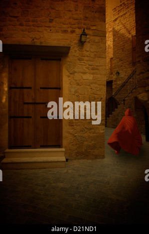 Mysterious figure in red cape running in the old village - Stock Photo