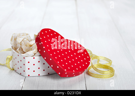 Gift box in shape of heart with golden ribbon on wooden background - Stock Photo