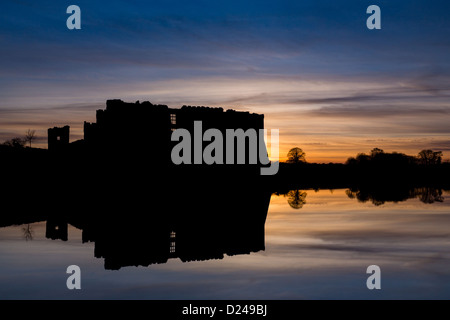 Carew Castle in Pembrokeshire, silhouette against sunset sky, in winter. Wales. - Stock Photo