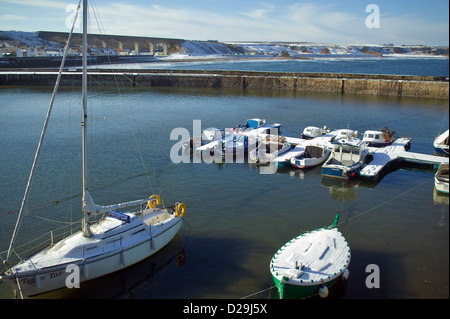 SMALL HARBOUR AT CULLEN  ON THE BANFFSHIRE COAST OF SCOTLAND IN WINTER WITH BOATS COVERED IN SNOW - Stock Photo