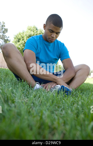 Young male African American college student taking a moment to stretch muscles and meditate on the grass field before - Stock Photo