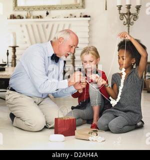 Older man and girls stringing popcorn - Stock Photo