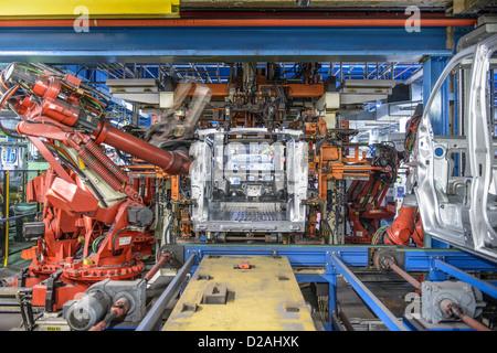 Robots welding van body in car factory - Stock Photo