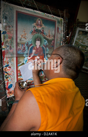 A Buddhist highly trained painter works on a painting in a gallery off the Bhaktapur Durbar Square. - Stock Photo