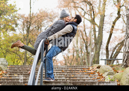 Couple kissing over park railing - Stock Photo