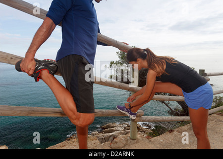 Couple stretching on dirt path - Stock Photo