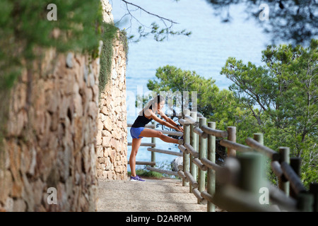 Runner stretching on dirt path - Stock Photo