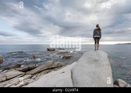 Woman on boulder overlooking ocean - Stock Photo