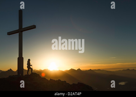 Hiker standing by cross on rocky hilltop - Stock Photo