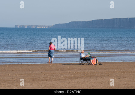 Holiday couple on quiet sandy beach (paddling sitting relaxing in sun) by calm blue flat sea - South Bay, Scarborough, - Stock Photo