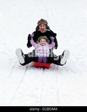 Father and his daughter having fun sledging on fresh snow - Stock Photo