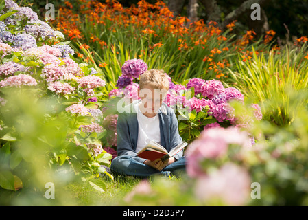 Boy reading in garden - Stock Photo