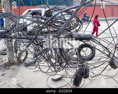An electrician works on a tangle of electric wires in Kathmandu, Nepal. - Stock Photo