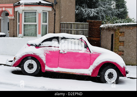 Pink Volkswagen car covered snow, Surrey, United Kingdom. - Stock Photo