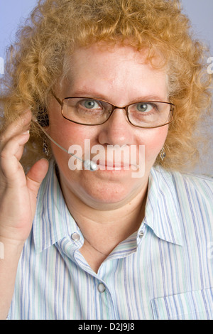 A mature woman taking a call on a hands free telephone headset - Stock Photo