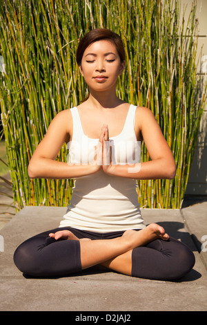 A young woman in a yoga posture with bamboo behind her; berkeley california united states of america - Stock Photo