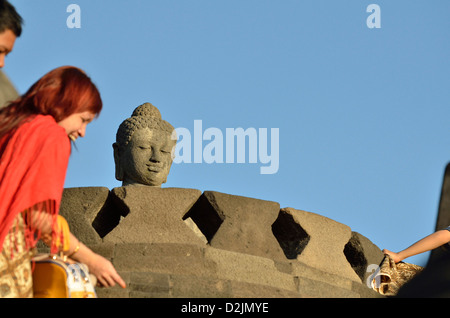 A tourist stand close to one of the Budfdha's head in the amazing temple of Borobudur; Central Java, Indonesia. - Stock Photo