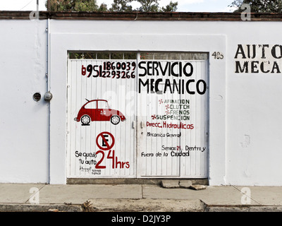 charming red & black sign hand painted on white gate in plaster wall advertising 24 hour auto mechanic service Oaxaca - Stock Photo