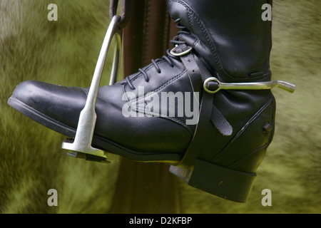 View of a horse rider's black riding boot sitting in a stirrup - Stock Photo