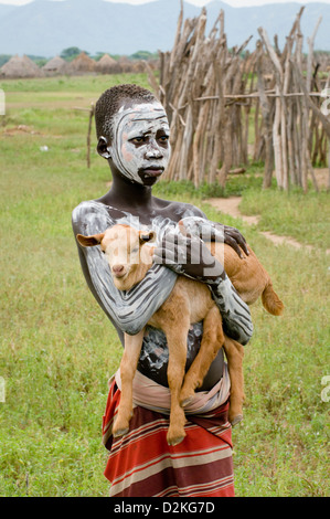 Portrait of decorated young Kara man holding baby goat - Stock Photo