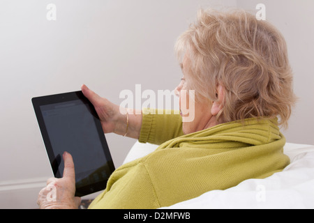 Mature lady using a digital tablet. - Stock Photo