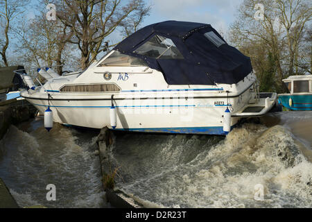 Little Baddow, Essex, UK. 31st January 2013.  A motor cruiser, Miss Behavin', sits precariously on a weir at Paper - Stock Photo