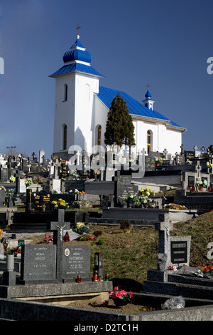 An old white chapel on a hill top over a cemetery in Slovakia - Stock Photo