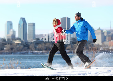 Happy couple snowshoeing in Montreal with cityscape skyline and river st. Lawrence in background - Stock Photo