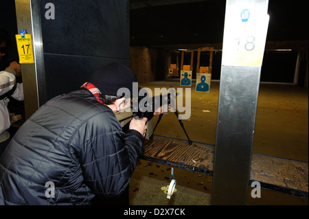 Target shooting with an AR-style target rifle at an indoor range - Stock Photo