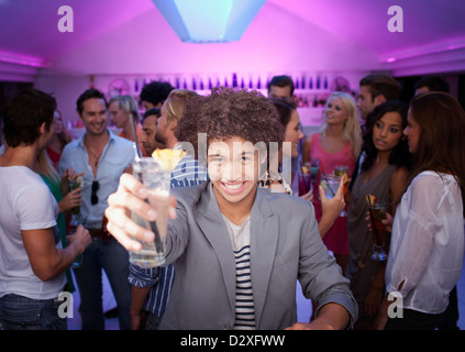 Portrait of smiling man holding cocktail at bar in nightclub - Stock Photo