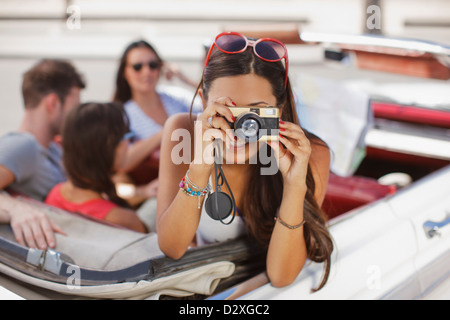 Woman taking picture from convertible - Stock Photo